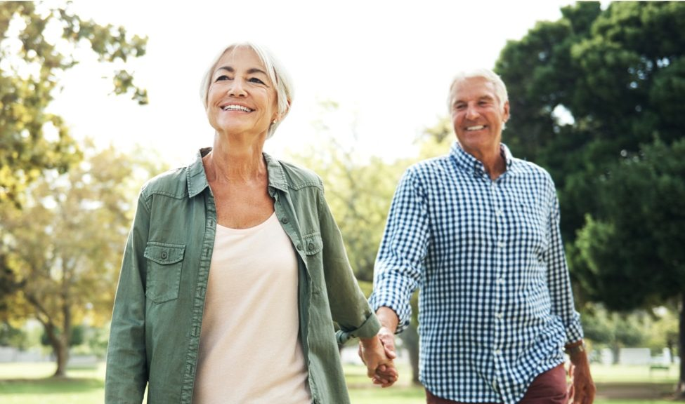 man and woman walking in park while holding hands