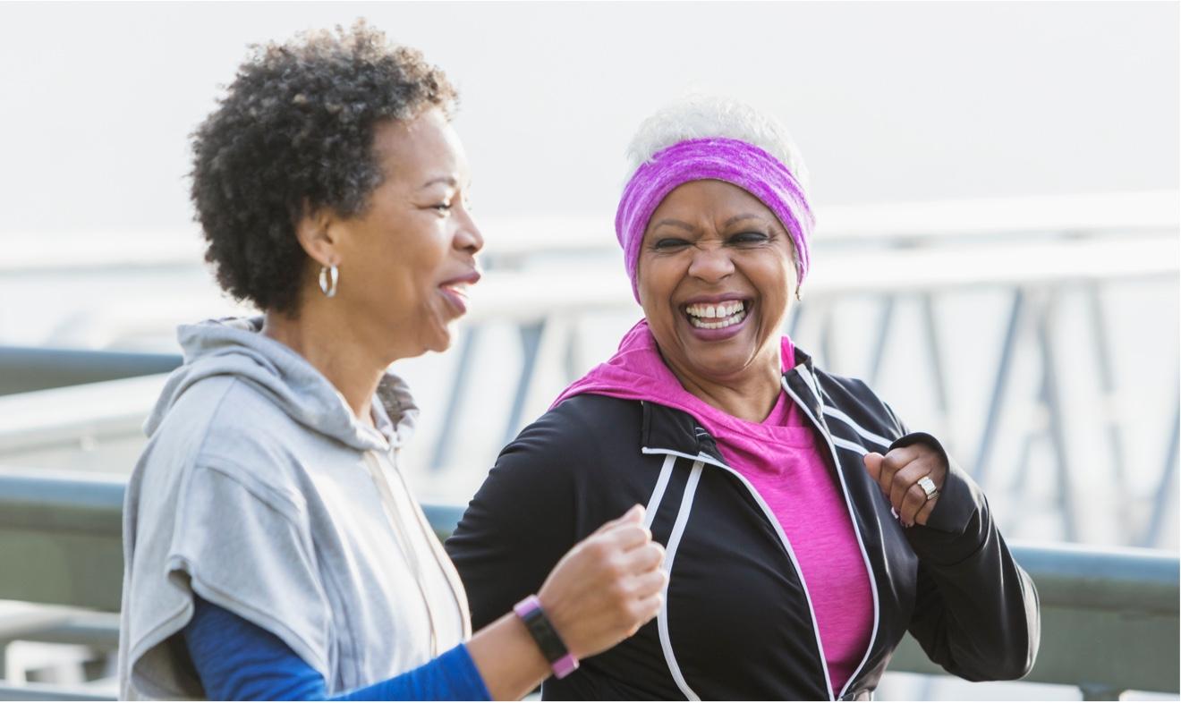 two women power walking near bridge