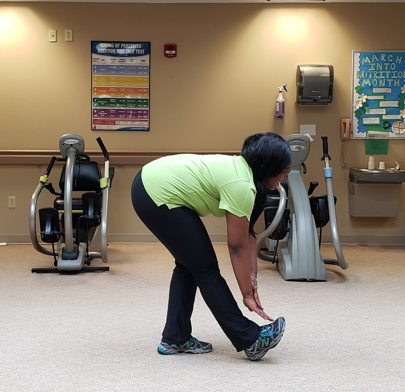 blog author Jasmine stretches to touch one out stretched foot with her hands
