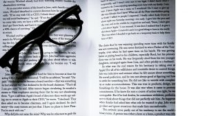 book open to pages with glasses lying across pages