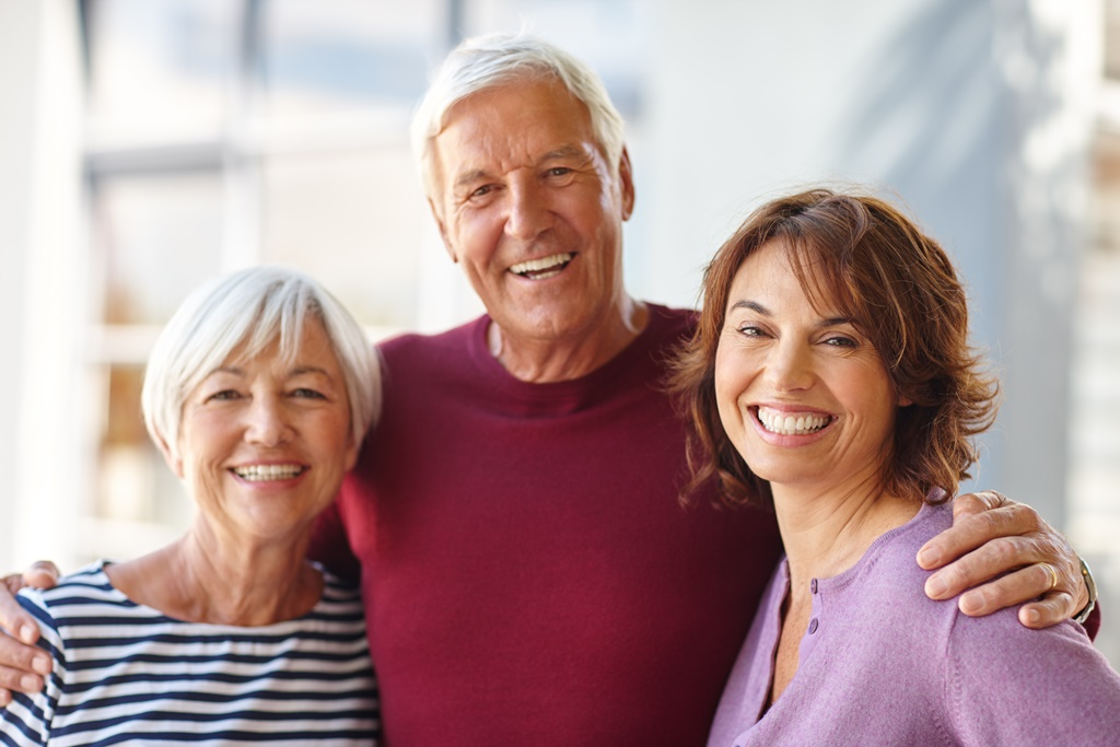 man with arms around wife and daughter