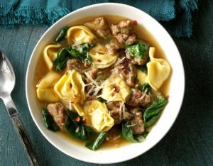 white bowl of sausage, spinach and tortellini soup