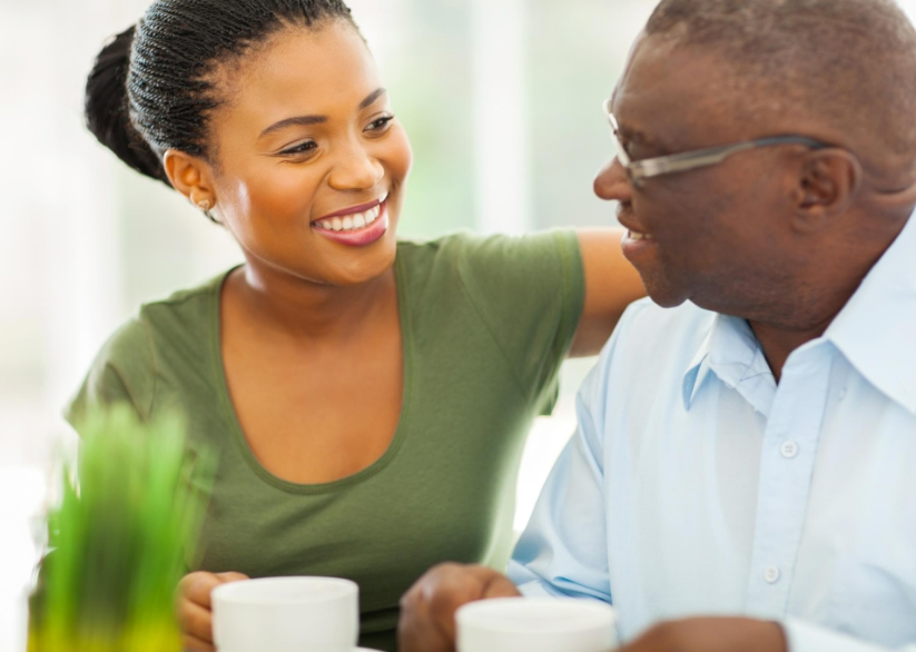 young woman having coffee with older man