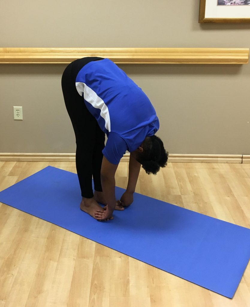 woman standing on yoga mat bend over nearly touching her toes