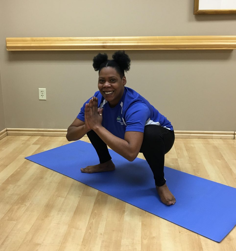 woman squatting on yoga mat with arms bent, palms pressed together