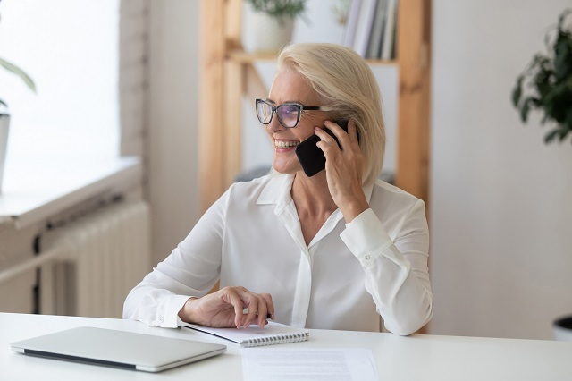woman on smart phone at desk
