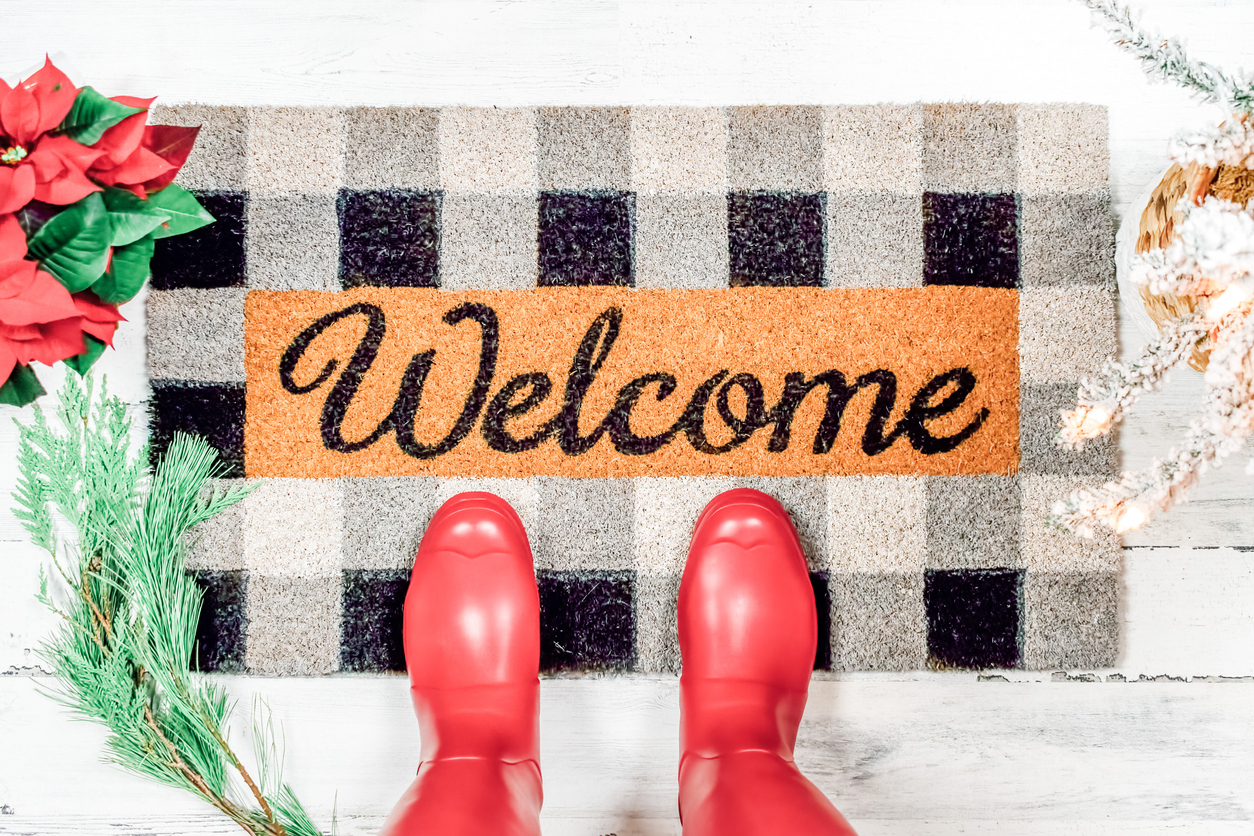 Holiday welcome mat with red boots on it